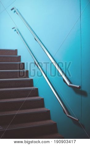 Staircase with stainless handrail on blue wall