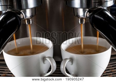 Espresso machine pouring two strong looking fresh coffee into a cups