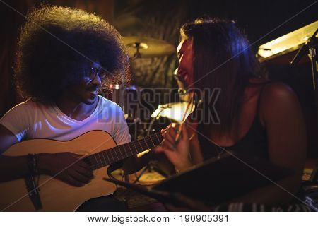 Smiling woman sitting with male guitarist practicing in nightclub