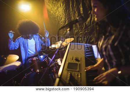 Female musician playing piano with male drummer in illuminated night club