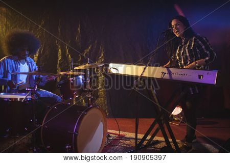 Female singer and male drummer performing in illuminated nightclub