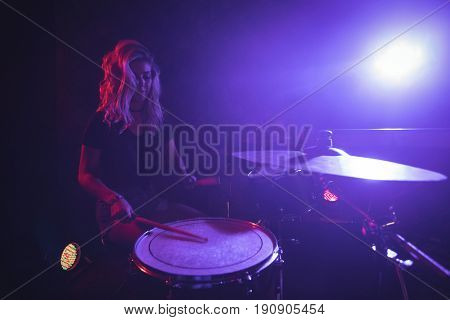 Confident female drummer performing on stage in nightclub