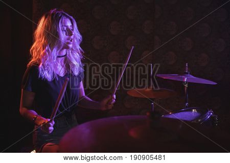 Confident female drummer performing on illuminated stage in nightclub