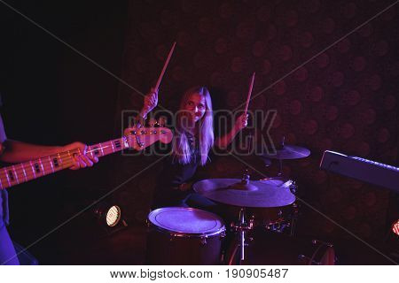 Confident female drummer looking at guitarist while performing on stage in nightclub