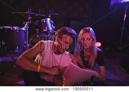 Young male and female musicians practicing with music sheets in nightclub