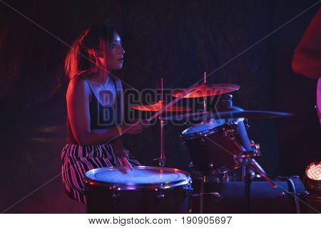 Female drummer practicing with drum kit in nightclub
