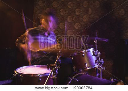 Blurred motion of male drummer performing in nightclub