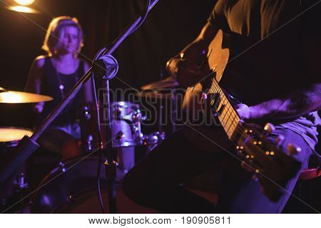 Mid section of male guitarist performing with female drummer in nightclub