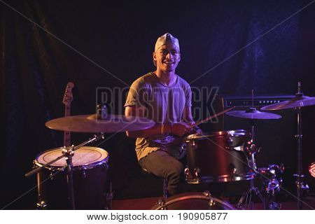 Portrait of male drummer performing in nightclub