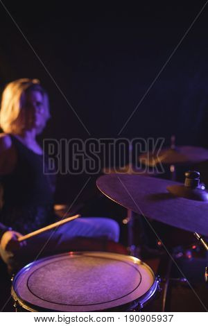 Confident female drummer performing in nightclub
