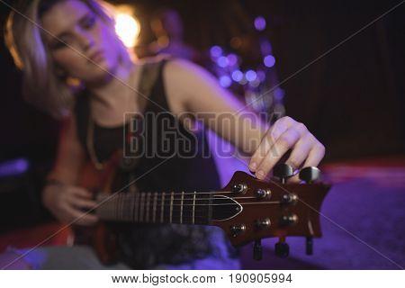 Female singer adjusting tuning peg of guitar in nightclub