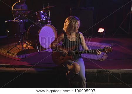 Female guitarist practicing while sitting on stage in nightclub