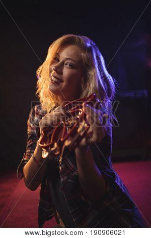Portrait of smiling female musician playing tambourine in nightclub