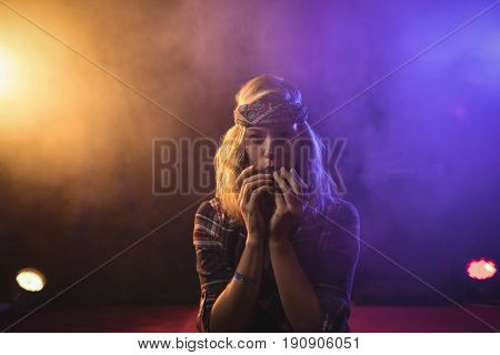 Portrait of confident female musician playing harmonica in illuminated nightclub