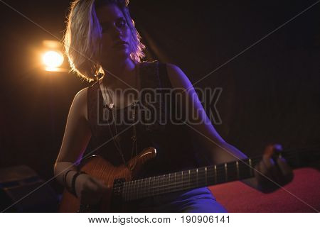 Low angle view of confident female guitarist performing in nightclub