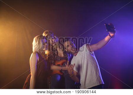 Enthusiastic fan taking picture with female performers in music concert