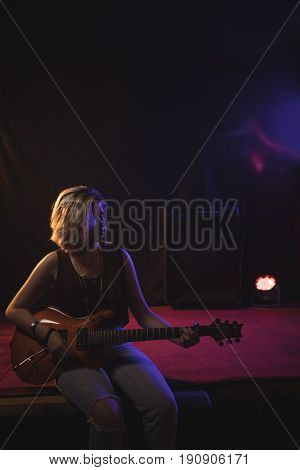 Confident female guitarist playing guitar while sitting on stage in nightclub