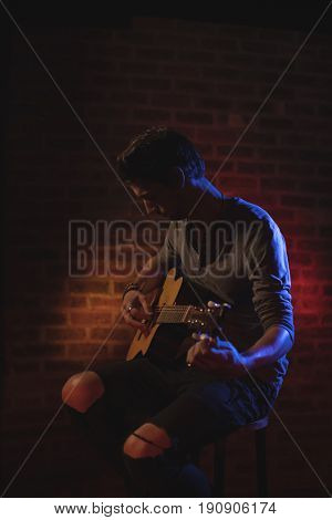 Young male guitarist performing in nightclub