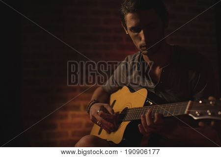 Confident male guitarist performing in music concert