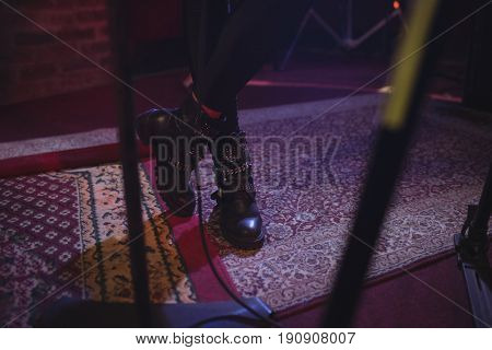 Low section of female singer standing on carpet in nightclub