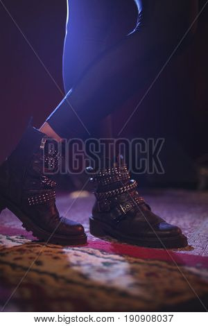 Low section of female singer wearing shoes while standing on carpet
