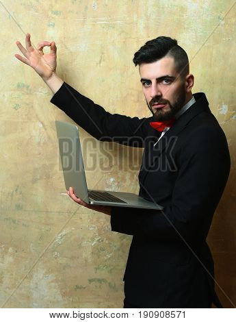 CEO with stylish beard haircut and strong confident face expression showing OK sign and holding modern computer in his hand on cracked old wall background of dirty beige colour. Success and business
