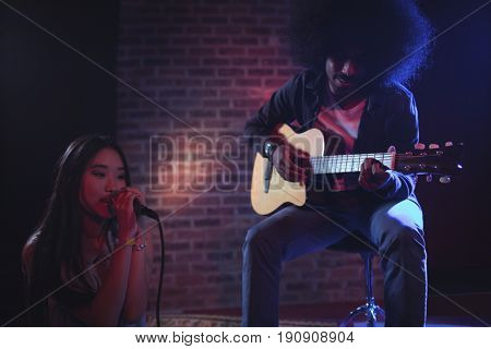 Female singer with male guitarist performing in nightclub
