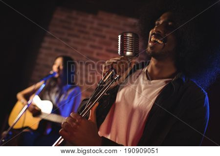 Cheerful male singer with female guitarist performing in nightclub