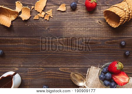 Fresh Berries, Waffle Cone And Chocolate Sauce On The Wooden Background, Top View. Ice-cream Backgro