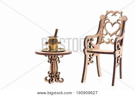 Antique mortar on tray on decorative wooden table with chair isolated on white background