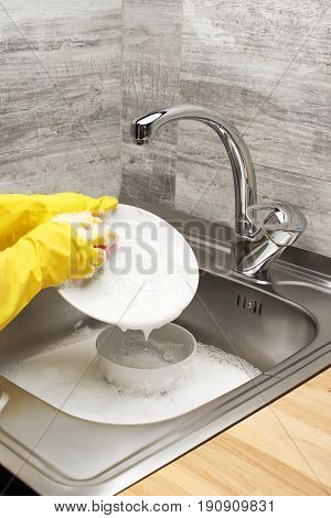 Hands In Gloves Washing White Plate Against Kitchen Sink