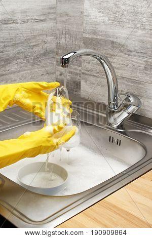 Hands Washing Glass Under Running Water Against Kitchen Sink