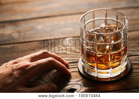 Glass of whiskey with ice cubes and man's hand on rustic wooden table with copy-space. Alcoholism concept.