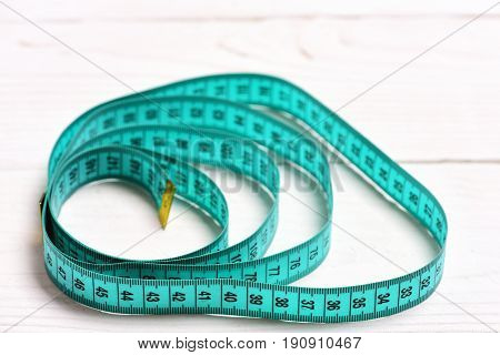 Circles Made Of Cyan Measuring Tape On White Wooden Background