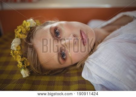 Portrait of young woman wearing flowers lying down in van