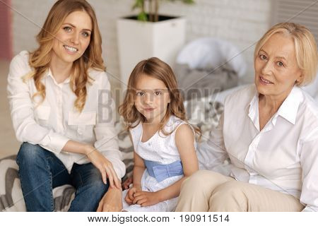 Pleasant time. Gorgeous little girl in a cute dress enjoying free time with her charming mother and grandmother while all of them sitting on the couch and posing for the camera