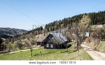 hamlets with wooden houses on settlement Mrackov bellow Jakubovsky vrch hill in spring Javorniky mountains in Kysuce region in Slovakia during spring day with clear sky