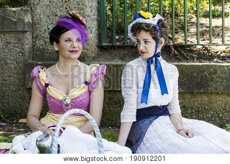 CAGLIARI, ITALY - MAY 29, 2016: Sunday at the Great Jatte VIII Ed. At the Public Gardens, couple of beautiful women in Victorian costume - Sardinia