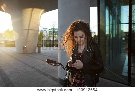 Young attractive female typing text message in chat to her best friend via smartphone. Pretty smiling curly young woman checking email box waiting her boyfriend in sun flare light summer evening