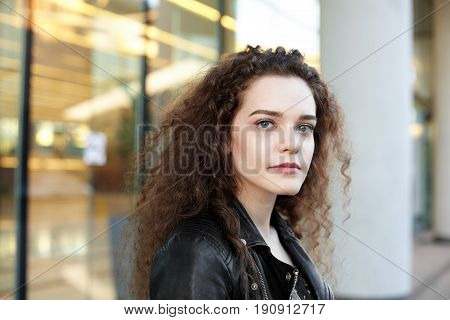 Close-up portrait of mindful Caucasian young attractive woman with dark curly hair staring at camera posing outside. Outdoor shot of confident good-looking girl with a serious thoughtful expression