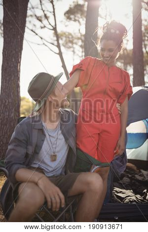 Smling couple looking at each other by tent at forest