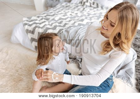 Delicate touches. Happy mother caressing her little daughter by holding her hands while having a smiley face painted with cream on her own hand