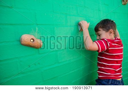 Rear view of boy climbing wall at playground in school
