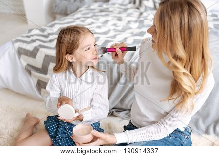 Cute moment. Pretty young mother holding a brush and applying with it some powder on the nose of her smiling daughter enjoying the process