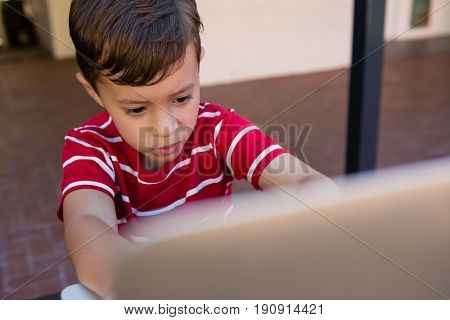 Close up of boy using laptop computer while sitting on chair at school