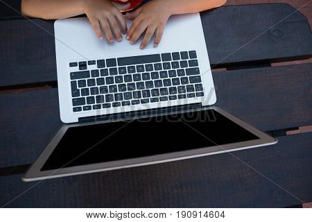 Overhead view of boy using digital laptop while sitting at table in school