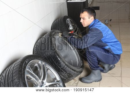 MOSCOW RUSSIA - OCTOBER 4 2015: The worker washes car rims with a soft brush with shampoo. Car service.