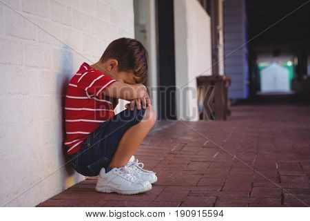 Side view of depressed boy crouching by wall at school building