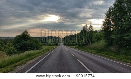 Country road Asphalt road through the tree clouds on blue sky in summer day at sunset scene with vintage tone Driving on an empty road