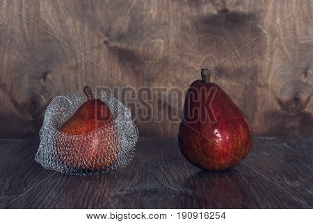 Two red pears on a wooden table one pear in a grid.Still life with pears